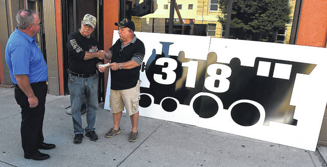 Tom Golden, center, receives a check Monday morning from Ray Magnus, along with Sam McLean, left, in front of a new sign for the 318 building on Main Street in Lima.