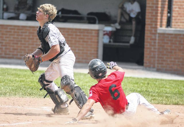 Shawnee's Justin Benke slides safely into home plate as Elida catcher Mike Niebel awaits the throw from the outfield during the District 5 ACME tournament Saturday.