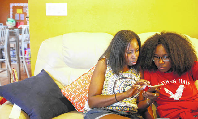 """Jennea Bivens, left, talks with her 13-year-old daughter, Ayrial Miller, about the contacts in her Snapchat social media account while sitting on the couch in their Chicago apartment June 18. Bivens uses a monitoring app to track and limit her daughter's phone use, but she says there's no replacement for a face-to-face conversation, especially about social media. Tracking her daughter's social media, she says, can be """"a full-time job."""""""