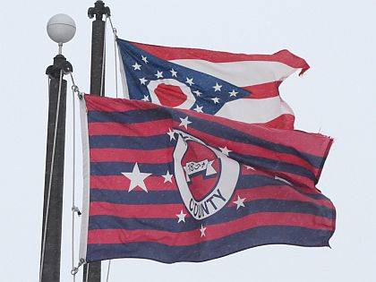 An Allen County flag and a State of Ohio flag are blown by a stiff wind Friday morning near the Veterans Civic Center in downtown Lima. Jay Sowers - The Lima News