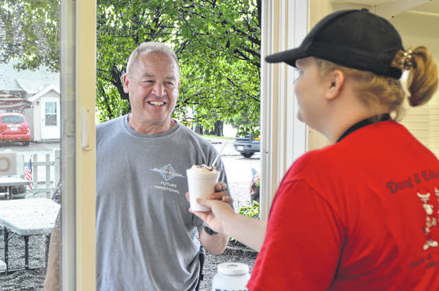 Doug and Edna's employee Miranda Niese, serves a sundae to former Putnam County Sheriff Tim Meyer at the ice cream shop, 417 W. Washington St., Pandora.
