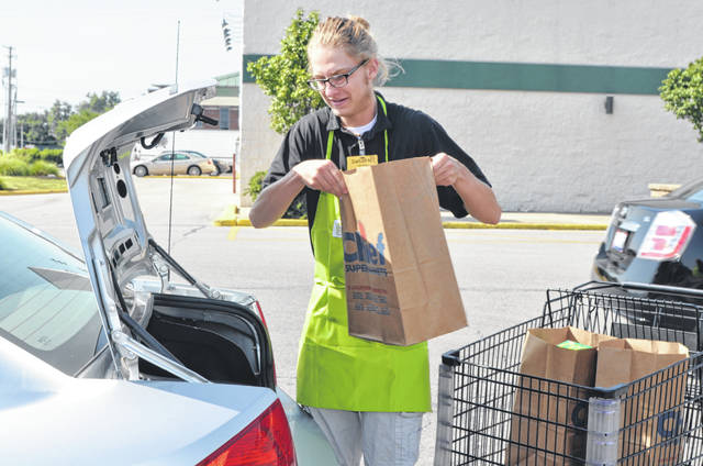Dalton Niese, a Chief Markets employee, places bags in the back of a Mobile Market customer's trunk at the grocer's Cable Road location.
