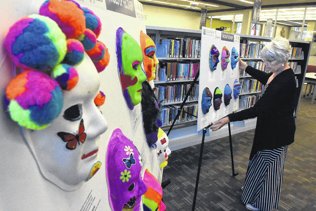 Karen Sommer, director of public relations at the Lima Public Library, sets up Faces of Recovery for display at the library. For the past year, Maha Zehery, outreach program liaison for Changing Seasons, has been promoting the Faces of Recovery mask project at different locations throughout Allen County. The masks were painted by individuals struggling with mental health issues and/or drug addition, as well as by local residents and Lima school students.