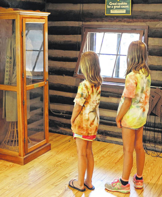 Girl Scouts Elsa Hunter, 7, and Greta Hunter, 9, of Cincinnati, look over an old Girl Scout uniform inside Sweetbriar Lodge at Camp Woodhaven.