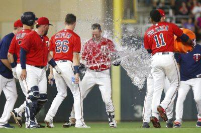 Minnesota's Jorge Polanco throws water on teammate Mitch Graver after Graver's fly ball to left field to win Monday night's game against Cleveland in Minneapolis. (AP photo)