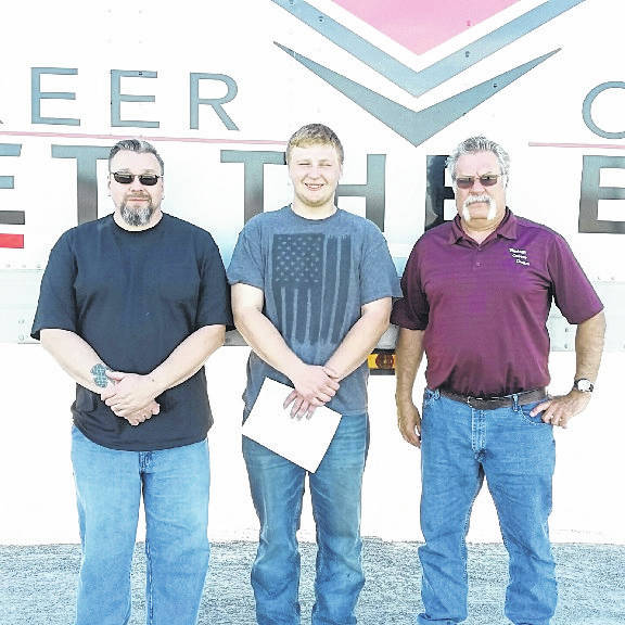 Lane Tuttle, the first Vantage high school CDL graduate, stands with CDL instructors Hartsel Bryant and Chuck Peters.