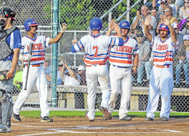 The Lima Locos' Brad Croy (7) celebrates with teammates, from left, Tyler Simon, left, Cade Beloso, and Anthony Amicangelo after scoring a run during Saturday night's game against Grand Lake at Simmons Field.