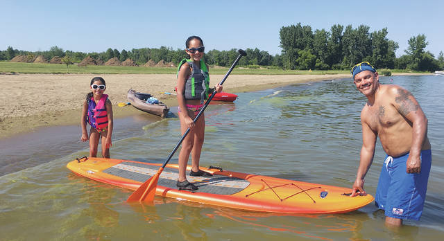 John Munoz and his daughters Ava and Mia, from near Delphos, enjoy a little sun and the water on the beach at Indian Lake's Old Field Beach.