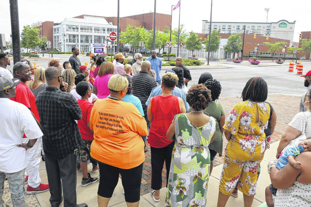 A group of people gather in Lima's Town Square to hear NAACP Lima Chapter President Ronald Fails discuss plans to file a class action lawsuit against the City of Lima over minority retention issues.