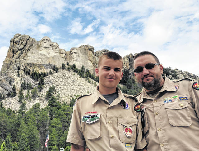 "Dylan and his father Chad Bryan pose in front of Mt. Rushmore. Members of Troop 84 had their trip to Philmont Scout Ranch canceled due to wildfires so they opted for ""Plan B."""