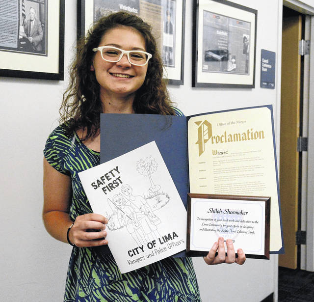 """Lima Senior graduate Shiloh Shoemaker shows off the """"Safety First"""" coloring book she helped design and a proclamation she was awarded recently by Lima Mayor David Berger."""