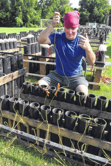 Dustin Socie, a pyro technician for Zambelli Fireworks prepares 4th of July fireworks during Mondays high temperatures while at Faurot Park. Zambelli will electronically ignite close to 2,500 fireworks on Wednesday.