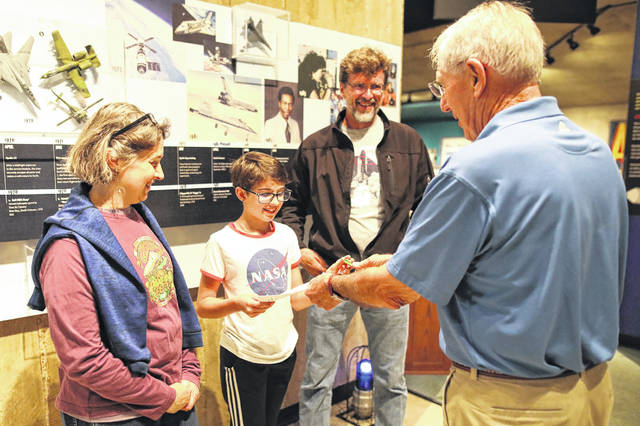 Retired astronaut Col. Robert Springer signs his autograph for 11-year-old Audrey Spooner pictured with her parents Marianne and John, of Marysville, during the expansion groundbreaking ceremony held at the Armstrong Air and Space Musuem on Friday afternoon.