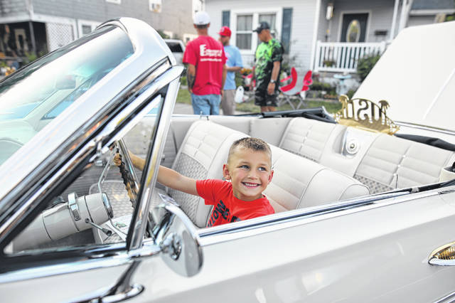 Six year-old Gage Spaugy, of Wapakoneta, sits in a 1965 Impala at the car show during the Cridersville Fireman's Jamboree on Friday evening.