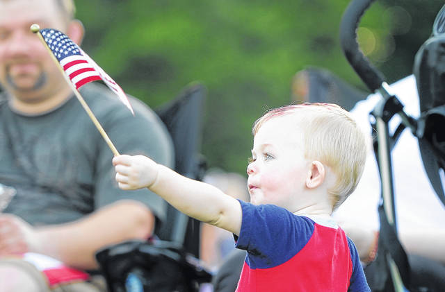 Bryson Nichols, 2, waves an American flag while listening to bands play prior to the fireworks Wednesday at the Star Spangled Spectacular in Lima's Faurot Park. The Fourth of July tradition marked its 25th year.