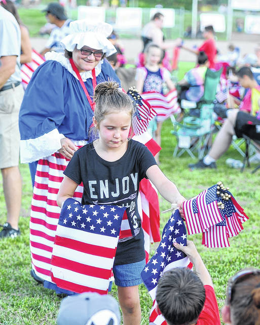 Hailey Maletich, 7, and Andrea Ahl pass out American flags prior to the fireworks at Faurot Park on Wednesday at the 25th annual Star Spangled Spectacular.