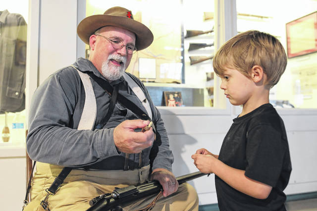 John Carnes portrays a Spanish/American War infantry soldier and shows four year-old Calvin Flory a Krag-Jorgenson gun and bullet during the live history event held at the Allen County Museum on Saturday afternoon. Amanda Wilson -The Lima News