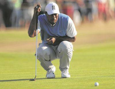 Tiger Woods lines up a putt on the 13th green during Thursday's first round of the British Open in Carnoustie, Scotland.