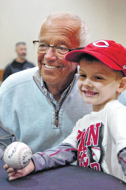 Broadcaster Marty Brennaman takes a photo with fan Aiden Kuhlman, of Ottawa, after signing his baseball during a past Reds Caravan tour.
