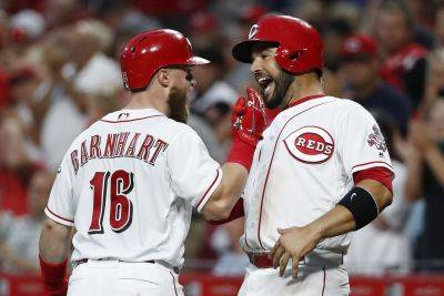 Cincinnati Reds' Tucker Barnhart (16) celebrates with Eugenio Suarez, right, after Barnhart hit a two-run home run off Philadelphia Phillies starting pitcher Ranger Suarez during the fourth inning of Thursday night's game in Cincinnati. (AP photo)