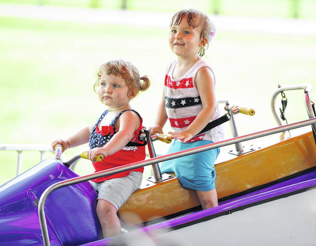 Sarah Reichenbaugh, 2, left, and Annabell Reichenbaugh, 3, enjoy a ride during Wednesday's Star Spangled Spectacular held at Faurot Park.