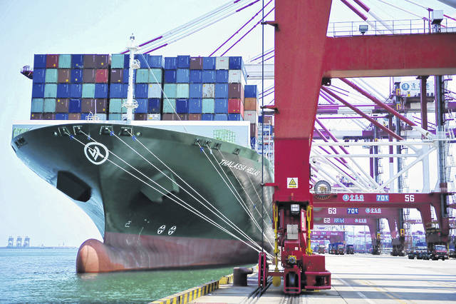 A ship hauls containers at a container port in Qingdao in eastern China's Shandong province Friday, July 6, 2018. The United States hiked tariffs on Chinese imports Friday and Beijing said it immediately retaliated in a dispute between the world's two biggest economies that President Donald Trump says he is prepared to escalate.