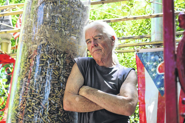 Jim Bowsher leans against a tube containing shell casings that represent the 71,388 Ohio men and women who died in wars.