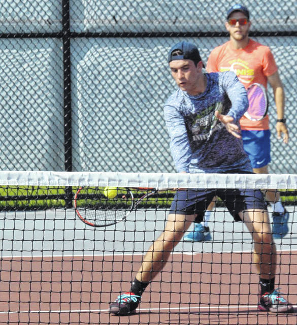 Michael Rutter plays a shot near thr net as teammate Jeff Brown watches from the baseline in the Lima Area Tennis Association Doubles Tournament on the courts at the University of Northwestern Ohio.