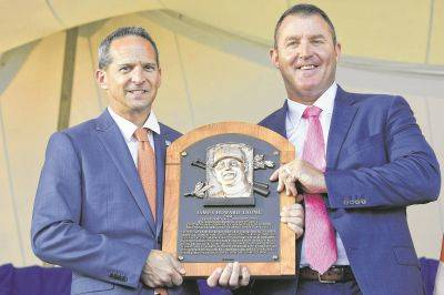 Hall of Fame President Jeff Idelson, left, stands with Jim Thome as they hold Thome's plaque during Sunday's induction ceremony in Cooperstown, N.Y.