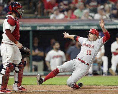 Cincinnati's Joey Votto, right, scores as Cleveland catcher Roberto Perez stands at home plate during the ninth inning of Tuesday night's game in Cleveland. The Reds won 7-4.