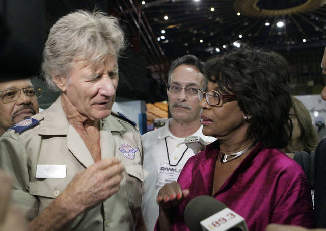 FILE - In this Aug. 11, 2009, file photo, Remote Area Medical founder Stan Brock, left, and Rep. Maxine Waters, D-Calif., talk at a large health care clinic set up by Remote Area Medical at the Forum in Inglewood, Calif. Brock, the founder of an organization that uses mobile medical clinics to bring health care services to people in remote, underserved areas of the U.S. and around the world, died in Tennessee on Wednesday, Aug. 29, 2018, Remote Area Medical says in a news release. He was 82. (AP Photo/Reed Saxon, File)