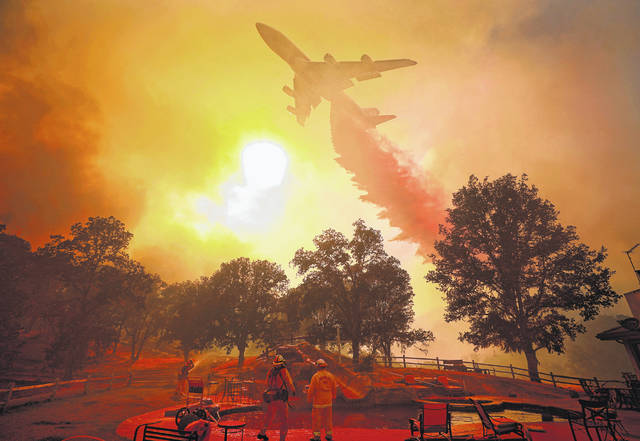 A 747 Global Airtanker makes a drop in front of advancing flames from a wildfire Thursday, Aug. 2, 2018, in Lakeport, Calif.