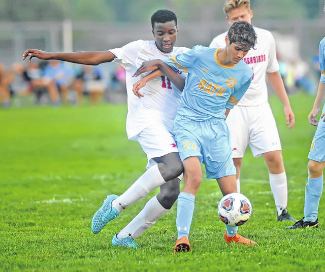 Lima Central Catholic's Odie Ugwanye, left, and Bath's Zach Garza fight for control during a Bath Kickoff Classic semifinal Tuesday night at Bath High School.