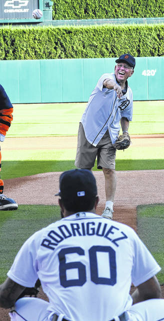 Bob Stolly, 84, of Lima, throws out the first pitch to Tigers catcher, Ronny Rodriguez, before the start of Friday night's Tigers game against Minnesota at Comerica Park in Detroit.