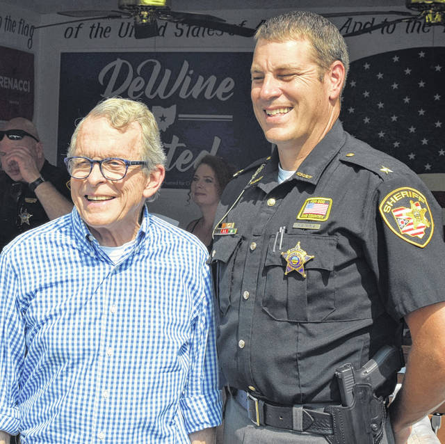 Ohio Attorney General and Republican gubernatorial candidate Mike DeWine poses with Allen County Sheriff Matt Treglia at the GOP booth at the Allen County Fair.