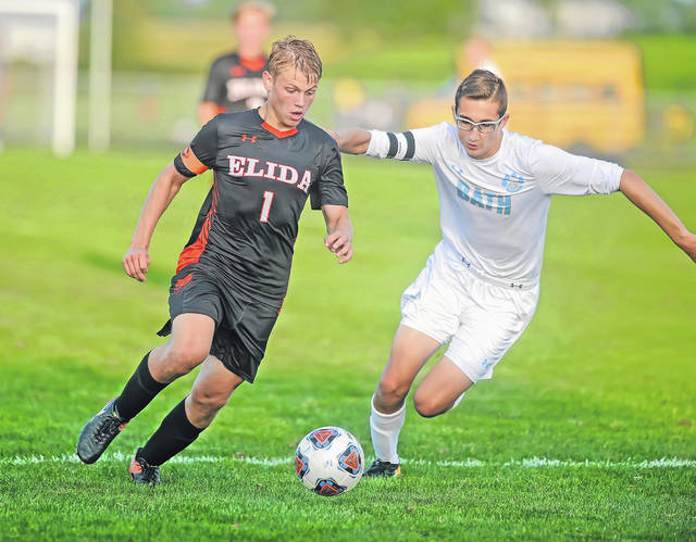 Elida's Draek Littler, left, and Bath's Robert Mooney battle for the ball during Thursday night's match at the Elida Sports Complex.