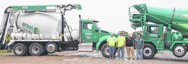 Ernst Concrete employees John Green, Collin Ernst, Harley Maize and Mark Green stand beside the newest concrete conveyor truck and the front discharge concrete mixer truck.