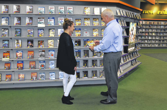 Family Video Regional Vice President Bill Mohler and Family Video employee Eden Allison browse through DVD selection at the Family Video on 733 S. Cable Road, Lima.