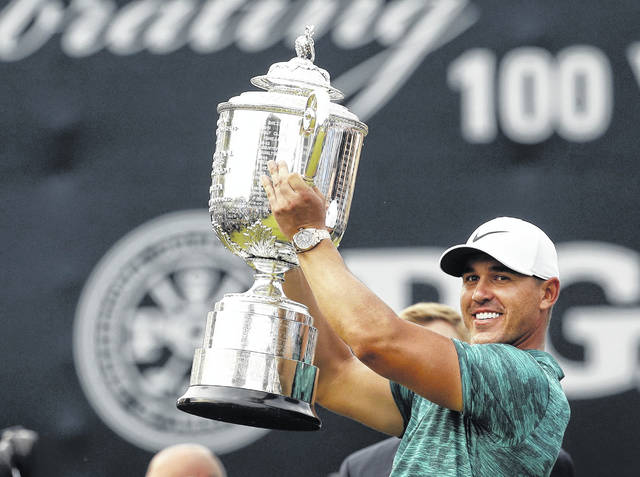 Brooks Koepka lifts the Wanamaker Trophy after winning the PGA Championship golf tournament at Bellerive Country Club, Sunday in St. Louis.It was his second major tournament victory this season.