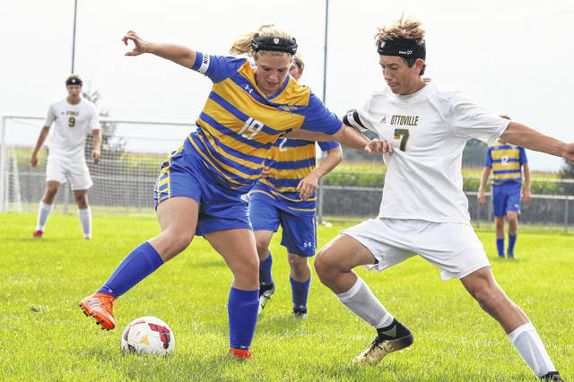 Lincolnview's Raegan Boley (19) shields the ball from Ottoville's Joe Miller during Friday night's match at Lincolnview.