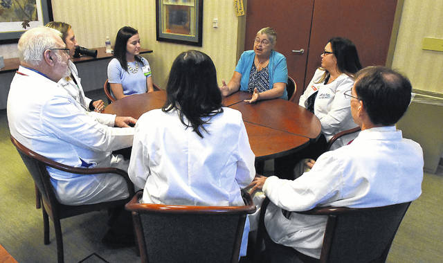 Vickie Wiechart, center, of Celina, attends a breast cancer clinic at Mercy Health-St. Rita's Cancer Center with her team of surgeons and oncologists. Attending the meeting are, Stacie Schuerman, PA, Dr. Nichole Nelson MD, Dr. Perry Williams MD, Dr. Ewa Mrozek MD, Dr. Michael Sheehan MD and Erin Bagan RN.