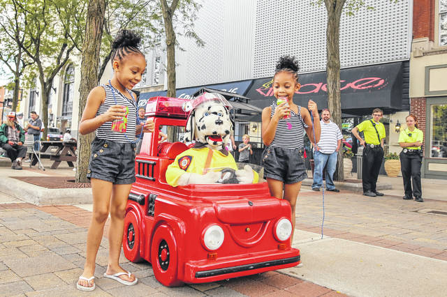 Twin five year olds Arazah and Aryiah Bowie of Lima enjoy a soda and festivities during the National Night Out in the square in 2015.