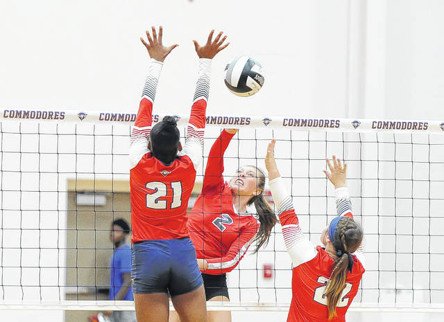 Delphos Jefferson's Courtney Teman hits a spikes against Perry's Tia Barfield, left, and Caitlin Shively during Tuesday night's match at Leonard V. Tolbert Gymnasium.
