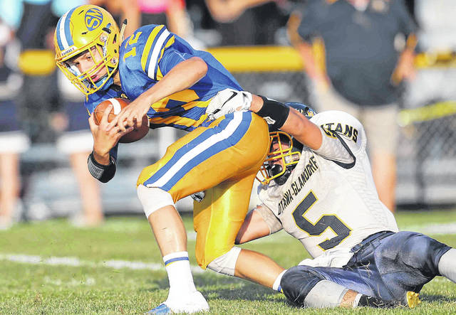 St. Marys' Ty Howell fights for yardage against Ottawa-Glandorf's Jasper Scarbery during Friday night's game at Skip Baughman Stadium in St. Marys. Howell scored a touchdown on offense and had an interception on defense for the Roughriders.