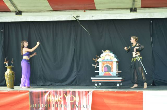 Isabella Bloom, left, catches swords her older sister Victoria Bloom tosses her as she removes them from the illusion prop their younger sister Elizabeth Bloom entered when the illusion began during a show by Grand Illusions by the Blooms during the Auglaize County Fair Wednesday evening.