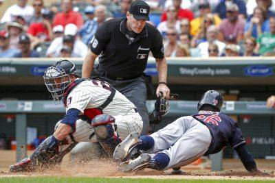 Cleveland Indians Rajai Davis, right, slides ahead of the play by Minnesota Twins catcher Mitch Garver to steal home as umpire Chris Conroy watches during Wednesday's game in Minneapolis. (AP photo)