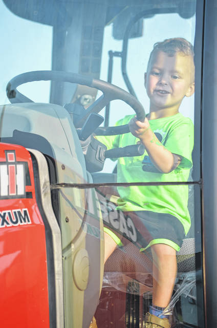 Braxton Bogart, 3, of Ottawa sits behind the wheel of a tractor during the 2017 Putnam County National Night Out Tuesday at Putnam Parkway.
