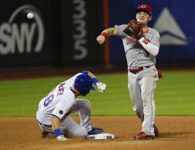 Cincinnati Reds' Scooter Gennett (3) throws out New York Mets' Wilmer Flores at first base after forcing out Jeff McNeil (68), for a double play during the eighth inning of a baseball game Tuesday, Aug. 7, 2018, in New York. (AP Photo/Frank Franklin II)