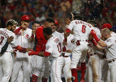 Teammates celebrate as the Reds' Phillip Ervin (27) crosses home plate with the game-winning run off San Francisco Giants relief pitcher Ray Black in the 11th inning of Friday night's game in Cincinnati. (AP photo)