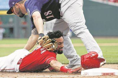 The Reds' Billy Hamilton is tagged out at third by Milwaukee's Mike Moustakas in the eighth inning of Thursday's game in Cincinnati.